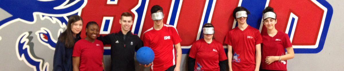 Photo de groupe de l'athlète Simon Richard et six élèves de l'école secondaire Monseigneur-Richard devant le logo de l'équipe sportive scolaire.