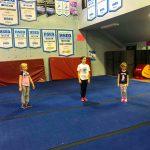 Programme Du sport pour moi! Printemps 2019 - Cheerleading. Capitale-Nationale. Élyana, Madeleine et Jeanne qui suient les instructions de Vicky.