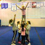 Programme Du sport pour moi! Printemps 2019 - Cheerleading. Capitale-Nationale. Élyana en équilibre dans les airs, surélevé par les jambes et Vicky qui lui rappelle la position des bras en V.