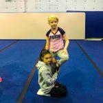 Programme Du sport pour moi! Printemps 2019 - Cheerleading. Capitale-Nationale. Élyana en équilibre sur une jambe, retenu par Noémie à genou.
