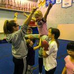 Programme Du sport pour moi! Printemps 2019 - Cheerleading. Capitale-Nationale. Élyana en grand écart, les bras en V, supporté par Noémie, Madeleine, Jeanne et Vicky qui lui montre de mouvement des bras.