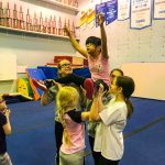 Programme Du sport pour moi! Printemps 2019 - Cheerleading. Capitale-Nationale. Amélie en grand écart, les bras en V, supporté par Noémie, Madeleine, Élyana et Vicky.