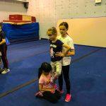 Programme Du sport pour moi! Printemps 2019 - Cheerleading. Capitale-Nationale. Amélie en position de base qui supporte sur sa jambe Jeanne en équilibre et Madeleine qui la retient en arrière.