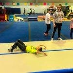 Programme Du sport pour moi! Printemps 2019 - Cheerleading. Capitale-Nationale. Félix sur le dos, qui termine d'exécuter une roulade, sous le regard de l'entraineuse.