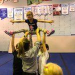 Programme Du sport pour moi! Printemps 2019 - Cheerleading. Capitale-Nationale. Jeanne en grand écart, les bras en V, supporté par Liam, Madeleine et Vicky.