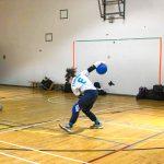 Goalball récréatif ASAQ – Hiver 2019. Le bras droit de Nathalie est étiré pour effectuer un lancer.