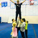Programme Du sport pour moi! Printemps 2019 - Cheerleading. Capitale-Nationale. Liam en équilibre dans les airs, surélevé par les jambes.