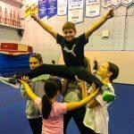 Programme Du sport pour moi! Printemps 2019 - Cheerleading. Capitale-Nationale. Liam en grand écart, les bras en V, supporté par Noémie, Madeleine, Amélie et Vicky.