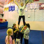 Programme Du sport pour moi! Printemps 2019 - Cheerleading. Capitale-Nationale. Madeleine en équilibre dans les airs, surélevé par les jambes.