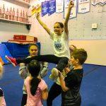 Programme Du sport pour moi! Printemps 2019 - Cheerleading. Capitale-Nationale. Madeleine en grand écart, les bras en V, supporté par Noémie, Liam et Vicky.