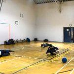 Goalball récréatif ASAQ – Hiver 2019. Nathalie, Sabrina et Raphaëlle sont couchées et s'apprêtent à recevoir le ballon.