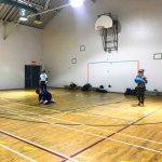 Goalball récréatif ASAQ – Hiver 2019. Raphaëlle est debout et a le ballon dans les mains pour lancer, Nathalie et Sabrina sont à sa droite.