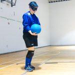 Goalball récréatif ASAQ – Hiver 2019. Sabrina est debout sur le terrain et tient le ballon avant de lancer.