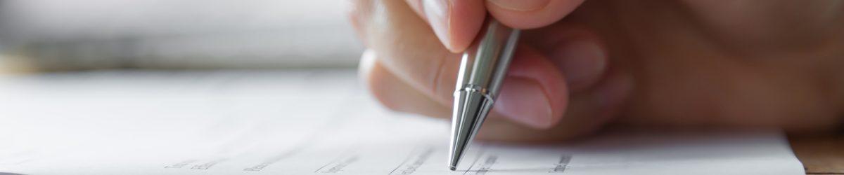 Main avec le stylo sur le formulaire de sondage.