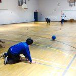 Goalball récréatif ASAQ – Hiver 2019. Vue des deux équipes sur le terrain, le ballon roule sur le jeu.