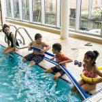 Du sport pour moi! - Natation. Montréal - Printemps 2019. Guity l'intervenante sportive, Marc-Antoine, Yacine et Hoa assient sur le bord de la piscine, prêts à commencer le cours.