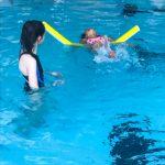 Du sport pour moi! - Natation. Montréal - Printemps 2019. Hoa qui nage sur le dos avec l'aide d'une nouille flottante, sous la supervision de Guity.