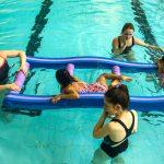 Du sport pour moi! - Natation. Montréal - Printemps 2019. Hoa qui nage traverse l'échelle flottante, sous le regarde des intervenantes.