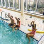 Du sport pour moi! - Natation. Montréal - Printemps 2019. Les enfants sont assis sur le bord de la piscine, les bras joints au-dessus de la tête, pour faire la fusée.