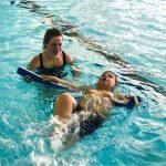 Du sport pour moi! - Natation. Montréal - Printemps 2019. Marc-Antoine qui nage sur le dos avec l'aide d'une nouille flottante, sous la supervision de Marie-Anne.