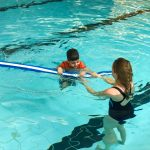 Du sport pour moi! - Natation. Montréal - Printemps 2019. Yacine qui reprend son souffle en nageant sur le dos, avec l'aide de Marie-Anne.