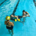 Du sport pour moi! - Natation. Montréal - Printemps 2019. Alexandra observe Marc-Antoine qui nage sur le côté avec l'aide de flotteurs aux mains et Raphaëlle pour les jambes.