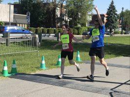 Défi DMLA 2019. Karine et Simon avec le bras gauche qui pointe vers le ciel, traverse la ligne d'arrivée à la course.