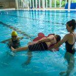 Du sport pour moi! - Natation. Montréal - Printemps 2019. Marc-Antoine apprend à nager de côté et mettre les jambes bien droites couché sur coussin flottant, Alexandra et Raphaëlle qui l'observe.
