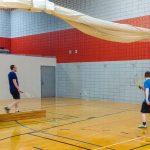Tennis sonore ASAQ Printemps 2019. Yan, Hugues et Danny s'entraînent contre le mur, vue de dos en diagonale.