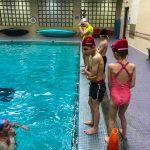 Programme Du sport pour moi! Printemps 2019 - Natation. Capitale-Nationale - Printemps 2019. Camille donne les consignes pour les sauts aux enfants debout sur le bord de la piscine.