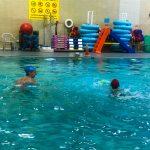 Programme Du sport pour moi! Printemps 2019 - Natation. Capitale-Nationale - Printemps 2019. Camille regarde Lou-Félix traverser la piscine à la nage.