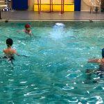 Programme Du sport pour moi! Printemps 2019 - Natation. Capitale-Nationale - Printemps 2019. Félix et Camille au centre de la piscine attendent que Jeanne traverse la piscine à la nage.