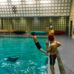 Programme Du sport pour moi! Printemps 2019 - Natation. Capitale-Nationale - Printemps 2019. Félix fait un saut du bord de la piscine, Madeleine et Lou-Félix le regarde faire.