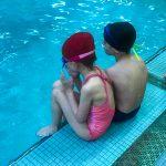 Programme Du sport pour moi! Printemps 2019 - Natation. Capitale-Nationale - Printemps 2019. Jeanne et Félix assient de dos, sur le bord de la piscine.