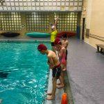 Programme Du sport pour moi! Printemps 2019 - Natation. Capitale-Nationale - Printemps 2019. Les enfants alignés debout sur le bord de la piscine pour faire de saut dans l'eau.