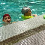 Programme Du sport pour moi! Printemps 2019 - Natation. Capitale-Nationale - Printemps 2019. Lou-Félix et Madeleine dans l'eau, sur le bord de la piscine.