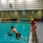 Programme Du sport pour moi! Printemps 2019 - Natation. Capitale-Nationale - Printemps 2019. Lou-Félix fait son saut dans l'eau, avec Jeanne, Félix et Madeleine alignés debout sur le bord de la piscine.