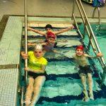Programme Du sport pour moi! Printemps 2019 - Natation. Capitale-Nationale - Printemps 2019. Photo de groupe. Madeleine et Lou-Félix à l'avant, Jeanne et Félix à l'arrière. Tous dans l'escalier de la piscine et souriants.