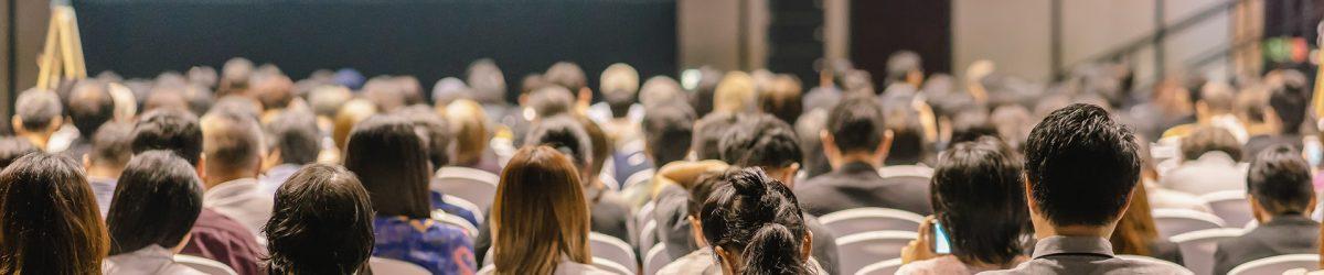 Vue arrière de l'audience à l'écoute des intervenants sur la scène dans une salle de conférence.