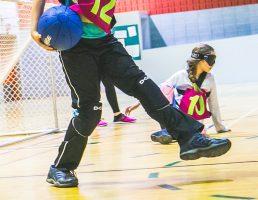 Mini-goalball-tournoi-2017. Ludo tient le ballon dans sa main droite, ses pieds sont orientés vers l'extérieur..