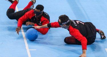 Bruno Haché et un coéquipier sont couchés sol, Bruno tente de prendre le ballon avec sa main droite. Crédit: IBSA Goalball.