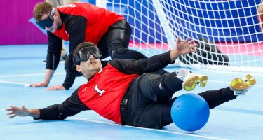 1. Ahmad Zeividavi, couché au sol, bloque le ballon avec ses pieds. Crédit-photo : IBSA Goalball