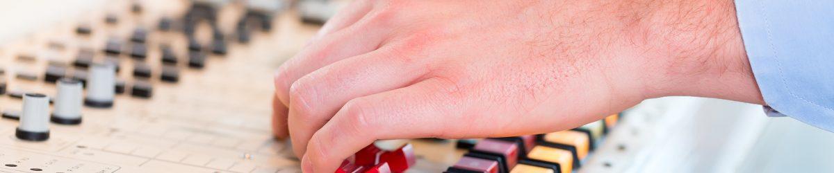 Mains d'un technicien radio manipulant la console dans une station de radio.