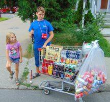 Ludovic et sa sœur avec le chariot rempli des bouteilles et des cannes vides