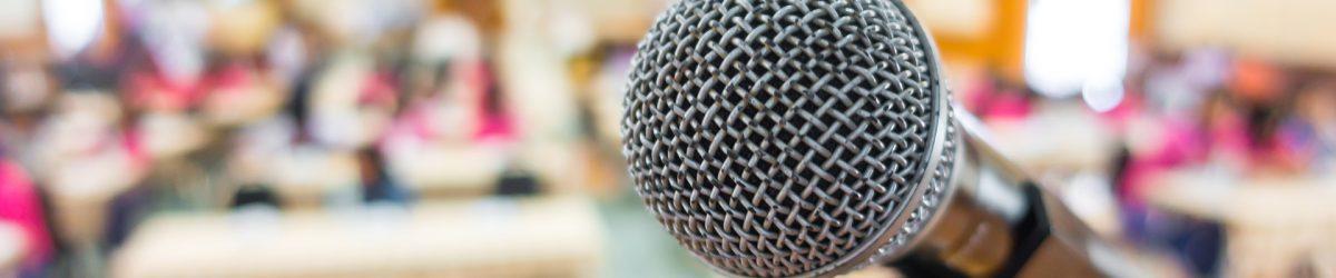 Microphone en premier plan dans une salle de conférence bien illuminée et colorée, au fond on voit des gens assis (fond flou artistique).