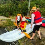 DSPM-Montréal-Automne 2019-Mayak. Clovis qui se prépare à aller sur l'eau à genoux sur le mayak, aidé par Danielle et sa maman.