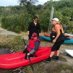 DSPM-Montréal-Automne 2019-Mayak. Marc-Antoine qui se prépare à aller sur l'eau à genoux sur le mayak, aidé par Danielle et sa maman.