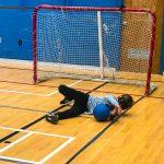 Mini-goalball Saint-Jérôme. Automne 2019. Ethan fait l'arrêt du ballon étendu sur le côté gauche.