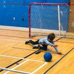 Mini-goalball Saint-Jérôme. Automne 2019. Ethan glisse sur le côté gauche pour arrêter le ballon qui arrive.