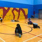 Mini-goalball Saint-Jérôme. Automne 2019. Les jeunes écoutent les instructions pour apprendre à glisser sur les côtés.